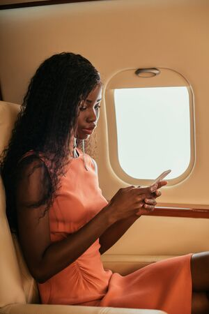 attractive african american woman chatting on smartphone in private jet