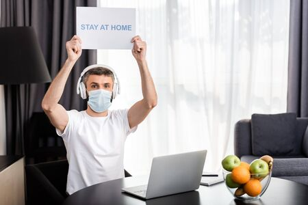 Freelancer in medical mask and headphones holding card with stay at home lettering near laptop and fruits on table