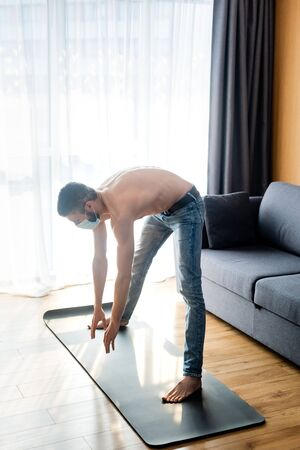 Side view of shirtless man in medical mask warming up on fitness mat at home