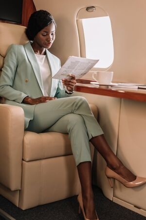 attractive african american businesswoman reading document in private plane