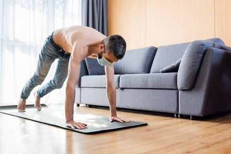 Shirtless man in medical mask working out on fitness mat at home