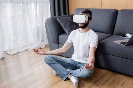 Man in vr headset meditating in lotus pose on floor in living room