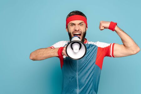 emotional stylish sportsman with loudspeaker showing muscles on blue background Archivio Fotografico