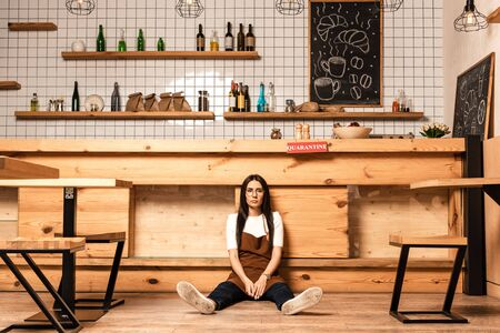 Cafe owner looking at camera and sitting on floor near table Фото со стока