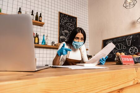 Shocked cafe owner in medical mask with papers pointing at calculator near laptop at table