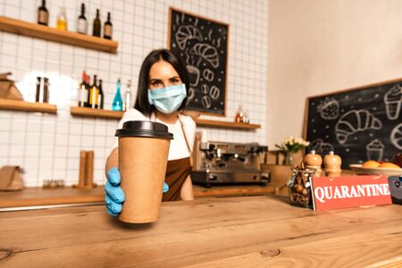 Selective focus of cafe owner in medical mask showing paper cup of coffee near table with card with quarantine inscription Фото со стока