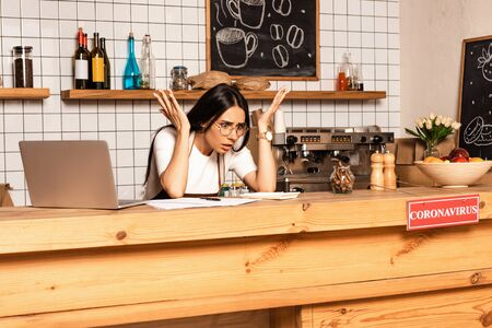 Shocked cafe owner looking at calculator near papers and laptop at table with card with coronavirus inscription Фото со стока
