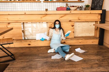 Cafe owner in medical mask holding documents with calculator and looking at camera near table on floor Фото со стока