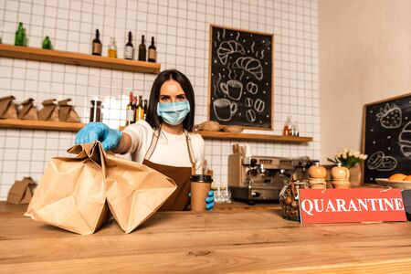 Cafe owner in medical mask with disposable cup of coffee showing paper bags near table with card with closed inscription Фото со стока