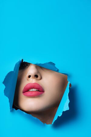Woman with pink lips looking across hole in blue paper 免版税图像