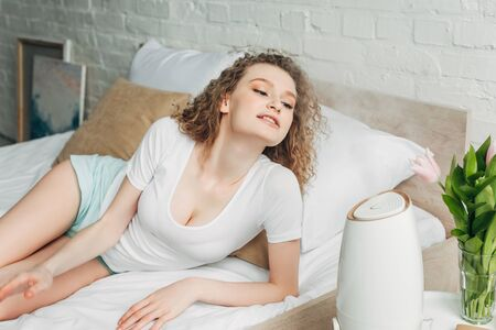 beautiful happy girl on bed with air purifier