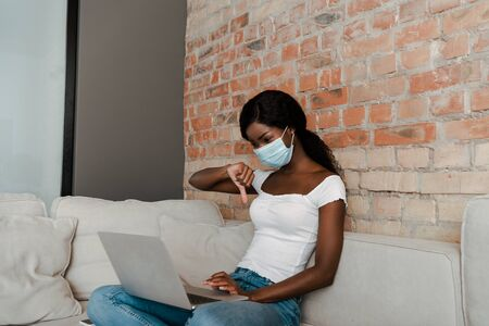 African american freelancer in medical mask with crossed legs and laptop showing dislike sign on sofa in living room
