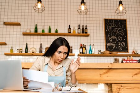 Shocked cafe owner with papers near laptop and glasses looking at calculator at table