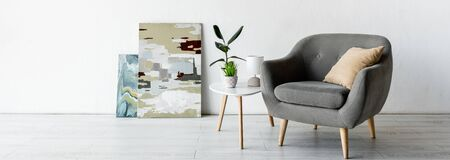 panoramic crop of comfortable armchair near coffee table with green plants, lamp and paintings in living room