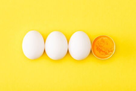 Top view of raw egg half among whole eggs on yellow background Archivio Fotografico