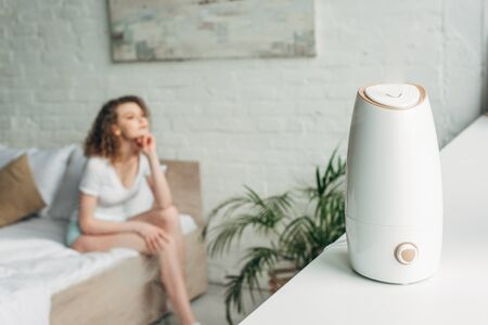 selective focus of attractive girl sitting on bed with air purifier on windowsill