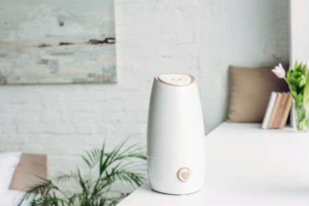 white humidifier standing on windowsill at home