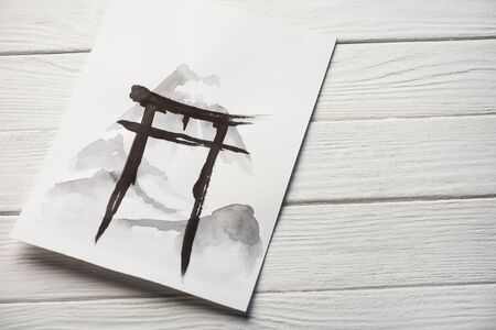 Top view of paper with japanese painting with hieroglyph on wooden background
