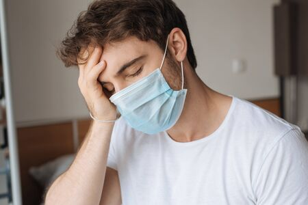 exhausted ill man in medical mask sitting in bedroom during self isolation