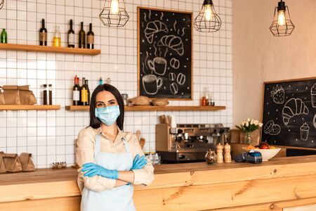 Cafe owner with crossed arms in medical mask and latex gloves looking at camera near table