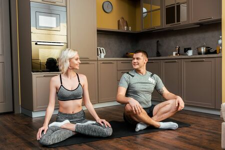 smiling young couple practicing yoga together in lotus pose at home during quarantine