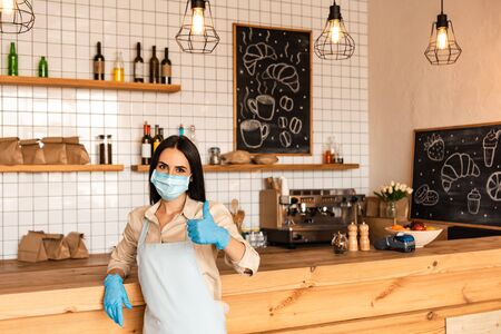 Cafe owner in medical mask and latex gloves looking at camera and showing like sign near table Фото со стока