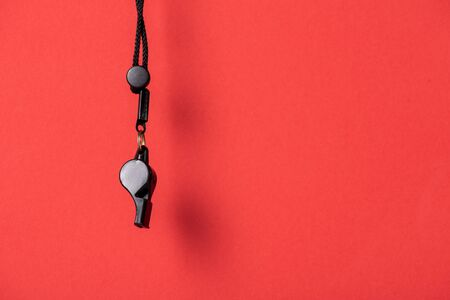 Black whistle with rope on red background