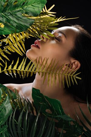 Sexy girl with closed eyes near monstera and fern green leaves isolated on black