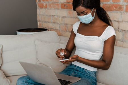 African american freelancer in medical mask with laptop disinfecting smartphone with hand sanitizer on sofa in living room