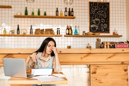 Tired cafe owner holding glasses near calculator, papers and laptop at table