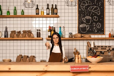 Brunette cafe owner looking at camera and showing dislike sign near table with card with coronavirus inscription Фото со стока