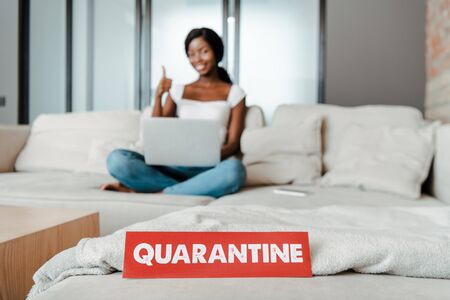 Selective focus of african american freelancer with laptop showing like sign and smiling on sofa with card with quarantine lettering in living room