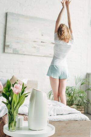 Back view of girl stretching in bedroom with air purifier and flowers, selective focus