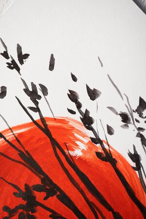 Top view of paper with Japanese painting with red sun and branches