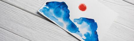 Top view of paper with Japanese painting with clouds and sun on wooden background, panoramic shot