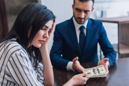 Selective focus of upset woman giving dollar banknotes to collector at table in room