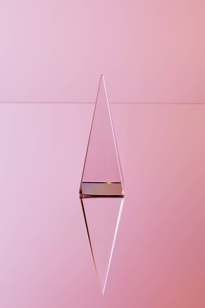 crystal transparent pyramid with reflection on pink background