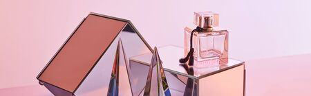 crystal transparent pyramid near perfume bottle and mirror cubes on pink background, panoramic crop Stockfoto