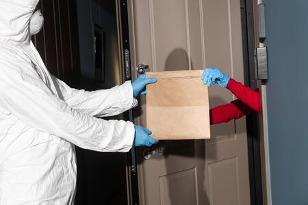 Side view of man in hazmat suit and medical mask giving package to woman in latex gloves near open door 版權商用圖片