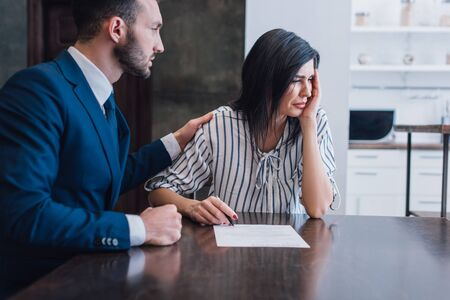 Collector reassuring upset woman with pen and document at table