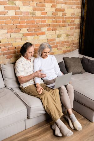 middle aged man pointing with hand at laptop near wife