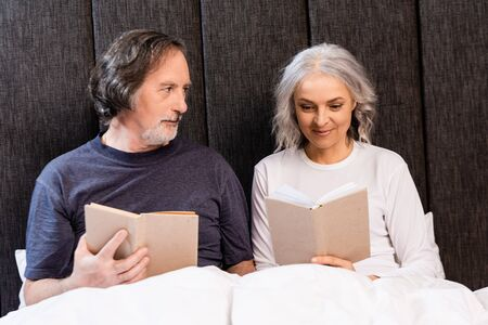 bearded mature man looking at happy wife reading book in bed