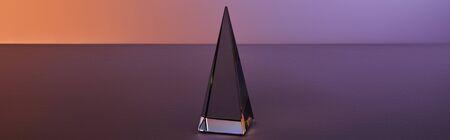 crystal transparent pyramid with light reflection on dark purple background, horizontal crop