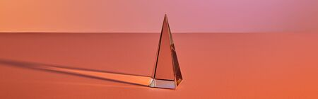 crystal transparent pyramid with light reflection on orange background, horizontal crop
