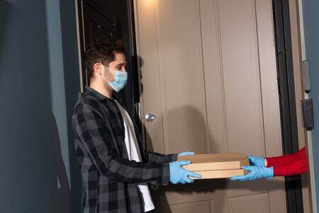 Side view of courier in medical mask giving pizza boxes to woman in latex gloves near open door on entryway 版權商用圖片