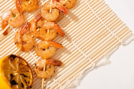top view of prawns on skewers with grilled lemon on bamboo mat on white background Фото со стока