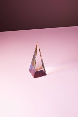crystal transparent pyramid with light reflection on pink background