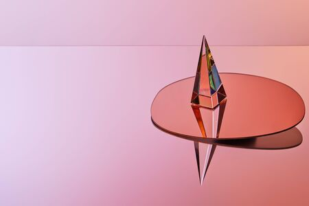 crystal transparent pyramid with reflection on round mirror on pink background