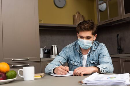 Selective focus of man in medical mask writing on notebook on kitchen table