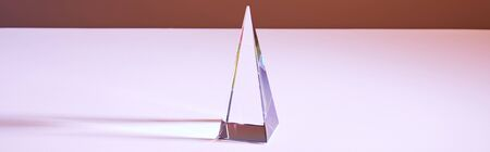 crystal transparent pyramid with light reflection on brown background, horizontal crop